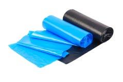 蓝色和黑垃圾袋卷在白色背景的 免版税库存照片