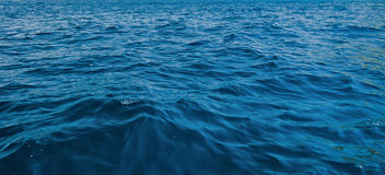 蓝色和黑暗的水表面 免版税库存图片