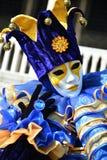 蓝色和黄色化装舞会服装的一个未认出的人与面具、说笑话者帽子有吵闹声的,蓝色圆环和手套在威尼斯狂欢节期间 免版税库存图片