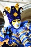 蓝色和黄色化装舞会服装的一个未认出的人与面具、说笑话者帽子有吵闹声的,蓝色圆环和手套在威尼斯狂欢节期间 库存照片