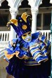 蓝色和黄色化装舞会服装的一个未认出的人与面具、说笑话者帽子有吵闹声的,蓝色圆环和手套在威尼斯狂欢节期间 库存图片