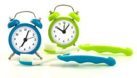 从蓝色和绿色时钟和牙刷的构成 免版税库存图片