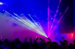蓝色和紫色激光束通过烟 免版税库存图片