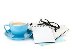 蓝色咖啡杯、玻璃和办公用品 库存照片