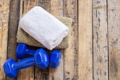 蓝色哑铃和毛巾在木桌上 免版税库存图片
