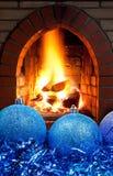 蓝色圣诞节球和闪亮金属片与壁炉 免版税图库摄影