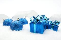 蓝色圣诞节礼物,中看不中用的物品变成银色在雪的丝带 免版税库存照片
