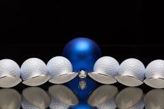 蓝色圣诞节装饰、六把匙子和高尔夫球 免版税库存照片