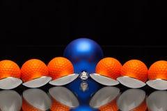 蓝色圣诞节装饰、六把匙子和高尔夫球 库存照片