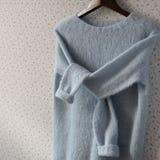 蓝色在挂衣架的被编织的羊毛毛线衣 免版税库存照片