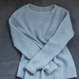蓝色在挂衣架的被编织的羊毛毛线衣 免版税库存图片