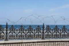 蓝色在有铁丝网的天蓝色的黑伪造的篱芭后看见 免版税图库摄影