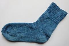蓝色在白色背景的颜色自然羊毛手工制造被编织的温暖的袜子袜子 库存图片