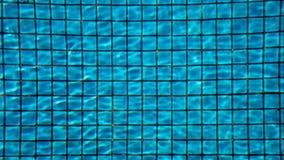 蓝色在背景中剥去了在游泳池的水与陶瓷砖马赛克 库存图片