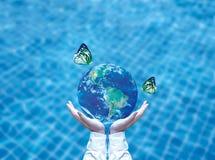 从蓝色地球的蝴蝶饮用水在手边 挽救水概念 免版税库存图片