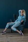 蓝色坐在椅子的衬衣和牛仔裤的年轻性感的白肤金发的妇女 免版税库存照片