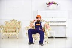 蓝色坐在葡萄酒扶手椅子的制服和橙色盔甲的工作者 皱眉和抬他的眼眉的有胡子的人 库存照片