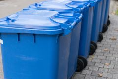 蓝色垃圾箱连续在街道上 库存图片