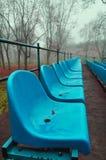 蓝色塑料位子行在秋天在有雾的天气停放 图库摄影