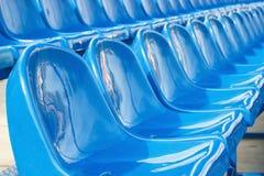 蓝色塑料椅子在体育场内 库存照片
