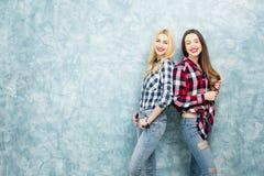 蓝色墙壁背景的女性朋友 库存照片
