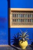 蓝色墙壁黄色花瓶 免版税库存图片