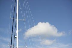 蓝色夏天天空蓬松云彩和游艇帆柱 免版税库存图片