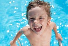 蓝色夏天室外水池的滑稽的矮小的白种人令人愉快的男孩 免版税库存照片