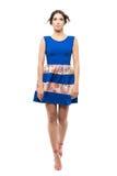 蓝色夏天礼服的年轻逗人喜爱的妇女走和查寻与有风飞行头发的 库存照片