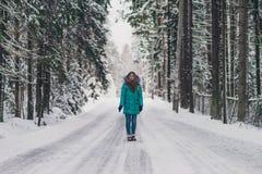 蓝色外套的女孩在冷的冬天森林快乐的冬天心情的路在妇女 免版税库存照片