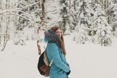 蓝色外套的女孩投掷在冷的冬天森林快乐的冬天心情的雪在妇女 免版税库存图片