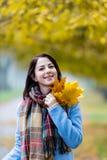 蓝色外套的深色的女孩有叶子的 免版税图库摄影