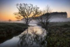 蓝色多云域草绿色早晨天空春天 一条美丽如画的河 图库摄影