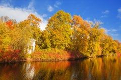 蓝色多云秋天域横向偏僻的天空结构树黄色 秋天公园、湖、叶子和太阳 库存图片