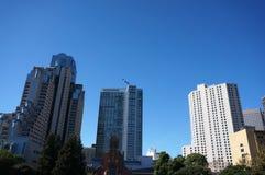蓝色天使在天空的形成飞行与摩天大楼下来 免版税库存照片