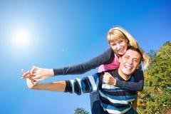 蓝色夫妇爱微笑在年轻人之下的天空 免版税库存照片