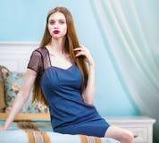 蓝色女睡衣的妇女在豪华卧室内部 免版税图库摄影