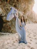蓝色婚礼礼服的新娘在日落或日出光的海滩 白肤金发的新娘礼服时装模特儿样式伞婚姻的白人妇女 图库摄影