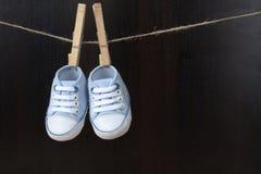 蓝色婴儿运动鞋垂悬了与在串的钳位 免版税库存图片