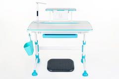 蓝色学校书桌、蓝色篮子、台灯和黑支持在腿下 免版税图库摄影
