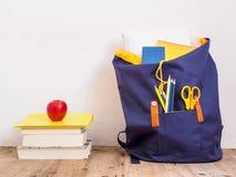 蓝色学校背包和堆在一个木地板上的书 库存图片