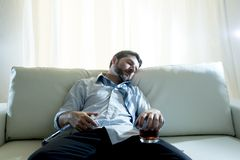 蓝色宽松领带睡觉的醺酒的商人喝与在长沙发的威士忌酒瓶 库存照片