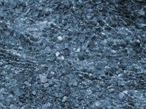 蓝色小卵石和波纹在水 库存图片