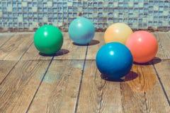 蓝色小球和许多在木地板上的五颜六色的小球设置与马赛克墙壁 免版税库存图片