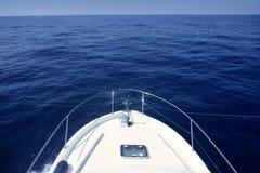 蓝色小船弓cruing的海运白色游艇 库存照片