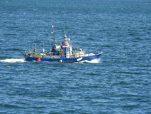 蓝色小船航行在海洋 库存图片