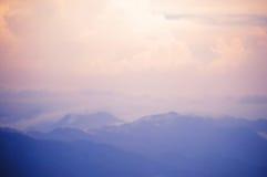 蓝色山和桃红色天空被弄脏的背景  免版税库存图片