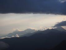 蓝色山脉晚上视图在阴霾的 云彩 免版税库存照片