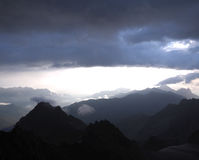 蓝色山脉晚上视图在阴霾的 云彩 库存图片
