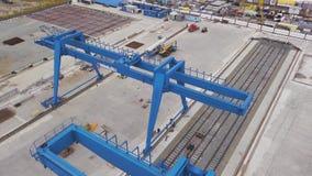 蓝色巨型桥式起重机身分的天线在路轨和具体基础 ?? 仓库顶视图与 股票视频